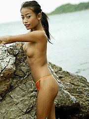 Very petite Thai girl strips elbow an distance from beach in thailand