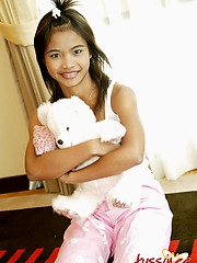Thai Teen Tussinee plays with a teddy bear in bed