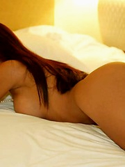 Sexy Thai model stripping and posing on a bed