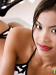 Petite Thai babe Tussinee strips out of her little bikini and shows her pussy