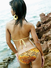Tussinee is at the beach taking pics in her yellow bikini