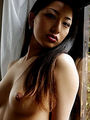 Japanese beauty reveals her nice tits as she slowly takes off her clothes