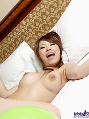 Lovely Asian model smiles as she shows off her big tits and tight ass and pussy