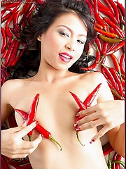 Naomi Chatee lays on a bed of hot peppers