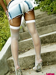 Hot babe Tussinee in cut off jean shorts and fishnets showing off outside