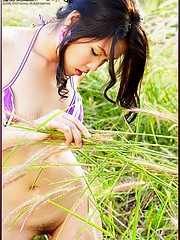 Aime Copony in a two piece bikini in the tall grass