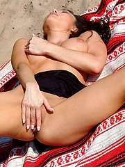 Busty slut relaxes while naked at the beach